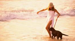 Mujer con perro en la playa.
